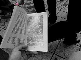 lecture d'un livre dans la foule, un soulier rose de femme dans le champs