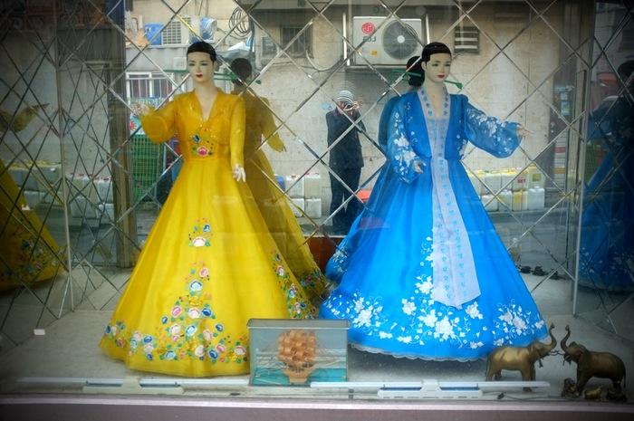 Deux mannequins dans une vitrine avec des robes