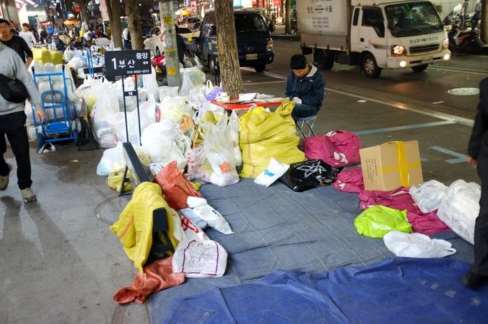 Homme et pile de sacs sur le trottoir