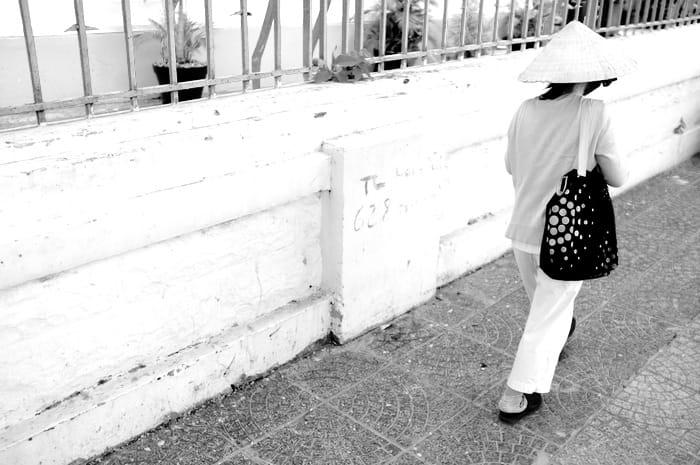 femme marchant sur un trottoir de dos