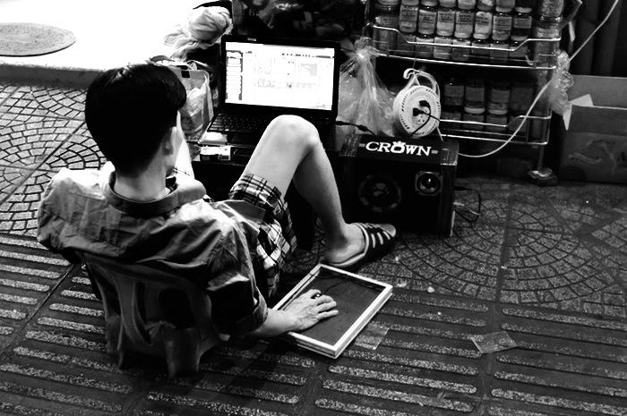 Homme utilisant un ordinateur dans la rue