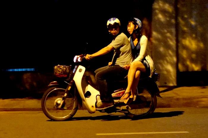 femme assise sur un scooter la nuit