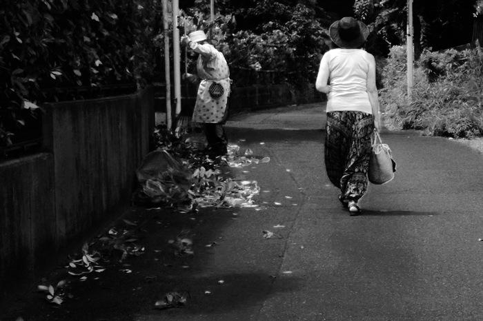 Une rue, deux femmes, et une haie coupée