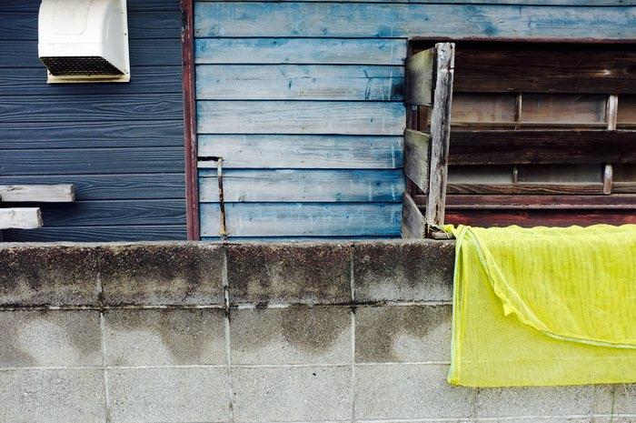 filet jaune sur un mur et maison bleue