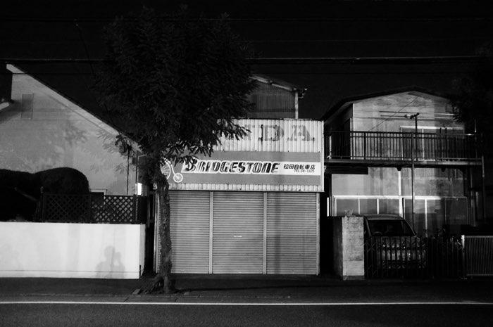 Vielles maisons le long de la rue dont enseigne Bridgestone