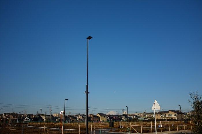 Cité de pavillons avec volcan et lune sur l'horizon