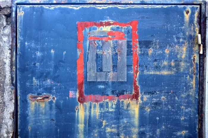 Porte bleue usée avec ruban collant rouge