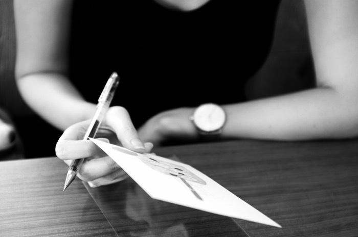 mains d'une femme et carte postale