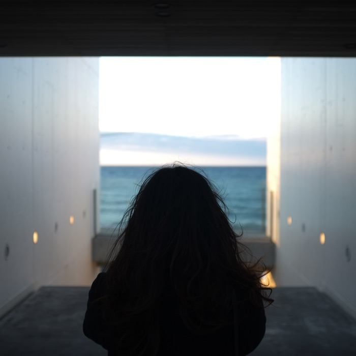 Femme de dos en face de la mer