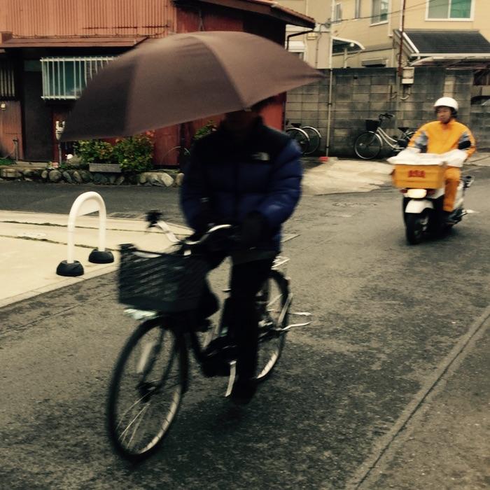 homme à vélo avec parapluie