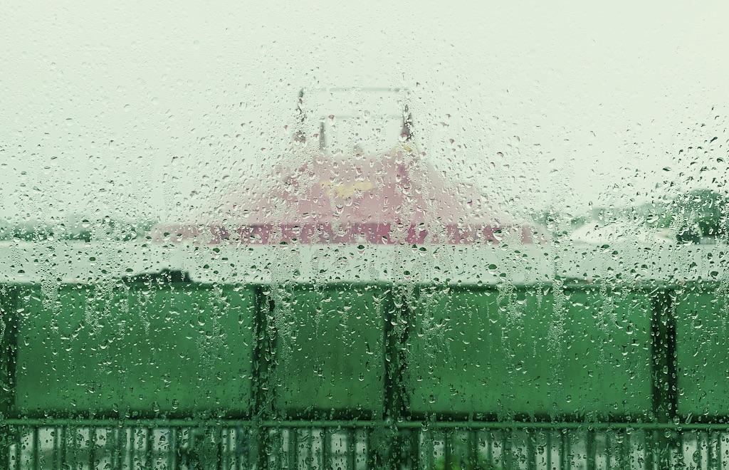 chapiteau derrière une vitre mouillée par la pluie