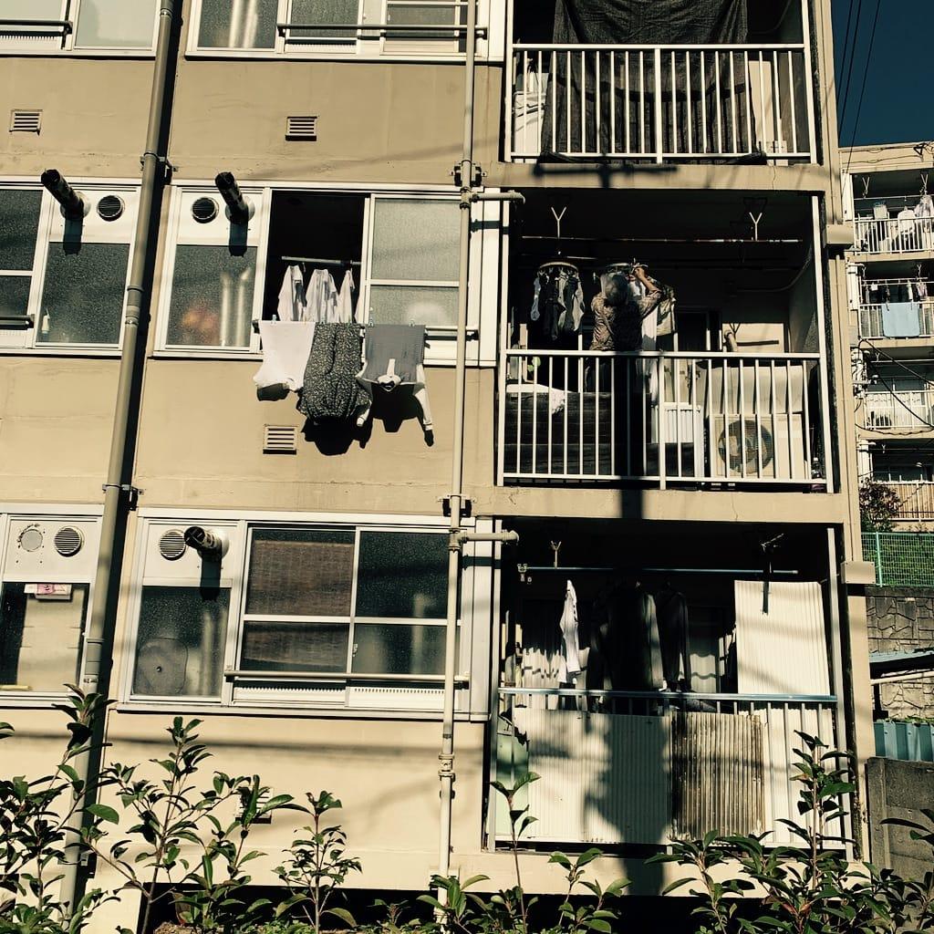 femme accrochant le linge sur son balcon