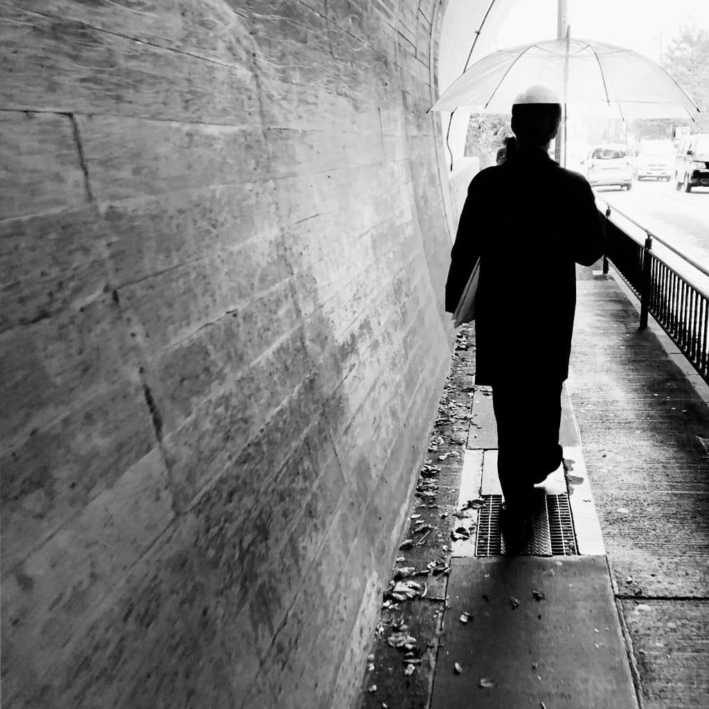 Homme au parapluie dans un tunnel