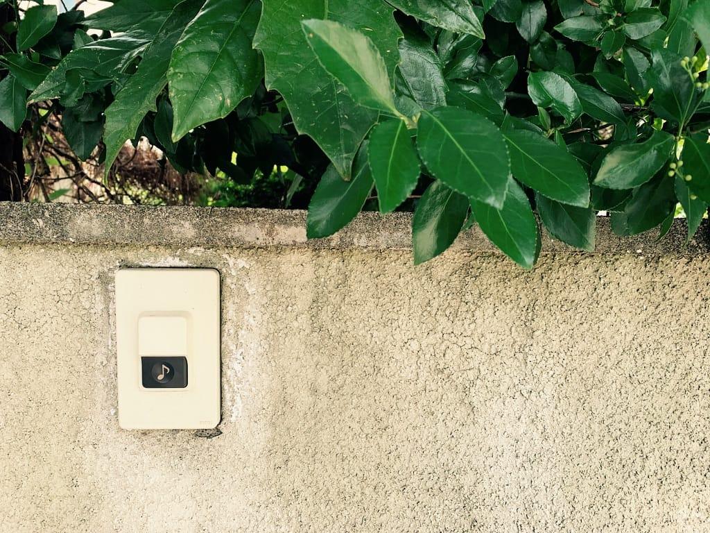 Sonnette sur un muret avec des feuilles.