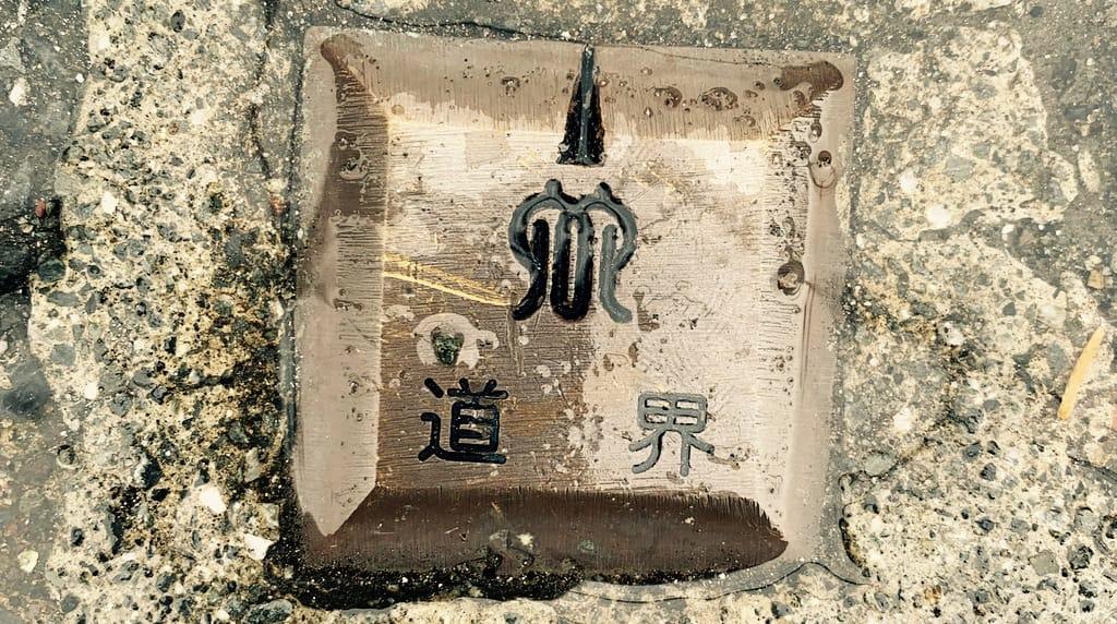 Caractères japonais écrits sur une plaque en métal dans le sol.