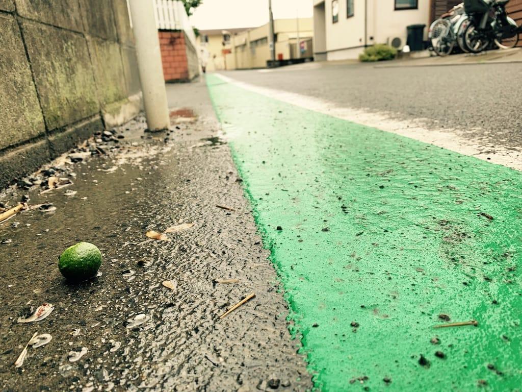 Citron vert sur la route près d'une bande verte.