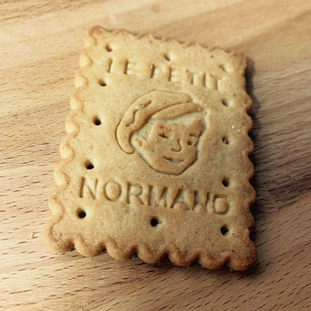 Biscuit avec un visage dessus et les mots le petit normand.