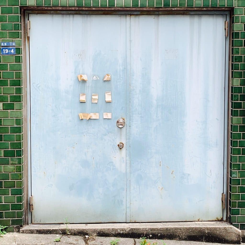Porte bleue en métal fermée et entourée de carrelages verts.