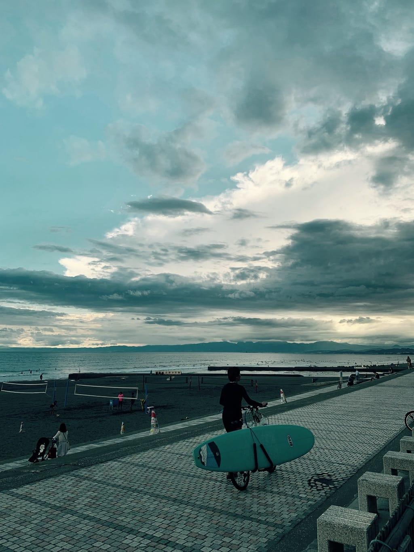 Un surfeur pousse son vélo le long de la plage, ciel nuageux.