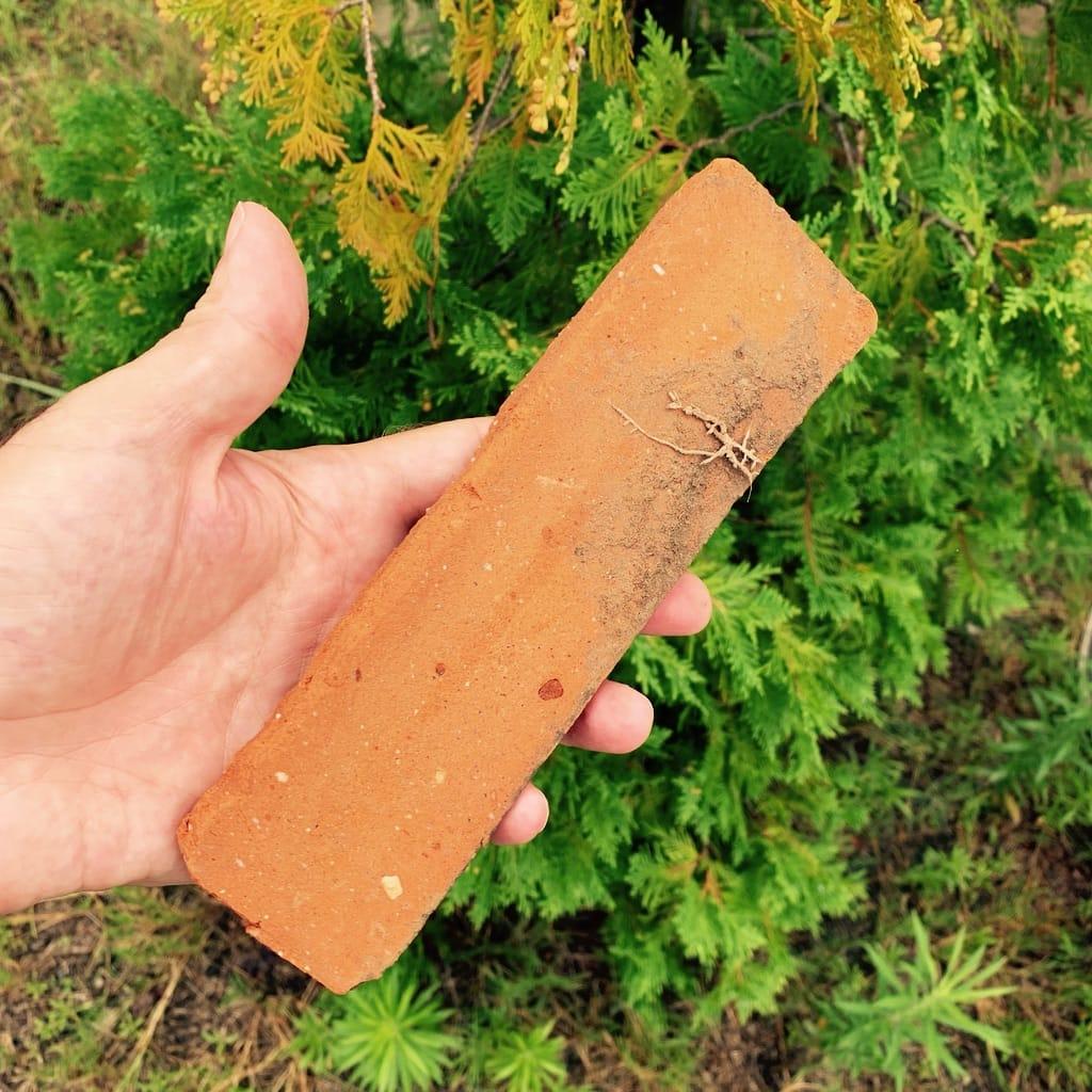 une brique dans une main.