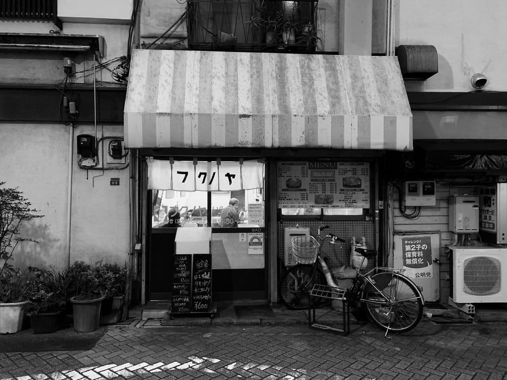 Vue d'un restaurant depuis la rue avec des clients à l'intérieur.
