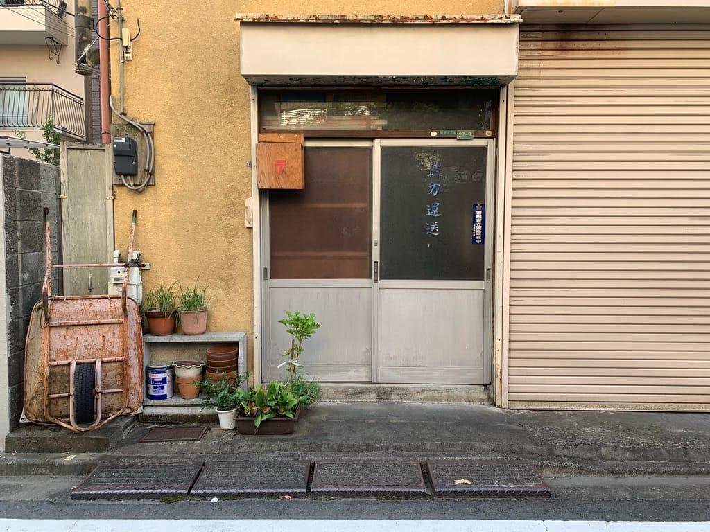 Porte d'entrée d'une maison avec fleurs et brouette.